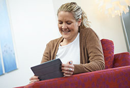 Middle aged woman sitting in armchair looking at tablet device and smiling