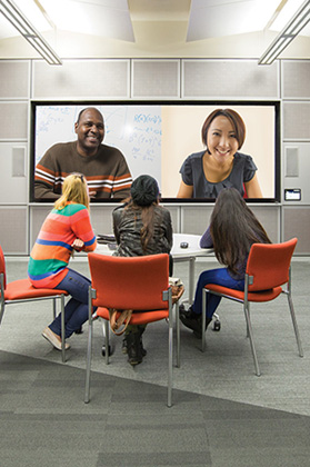 Students in a video conference sitting around a table viewing the attendees on screen.