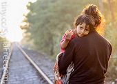 a woman carrying a child along a railway track.