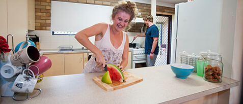 Female student cutting watermelon on bench of Wright Village kitchen with male student using stove in background