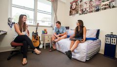 Three students in a Mary White College room with bed, office chair, and posters on wall