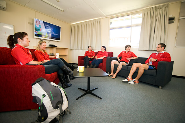 Six students sitting on lounges in Wright Village common room
