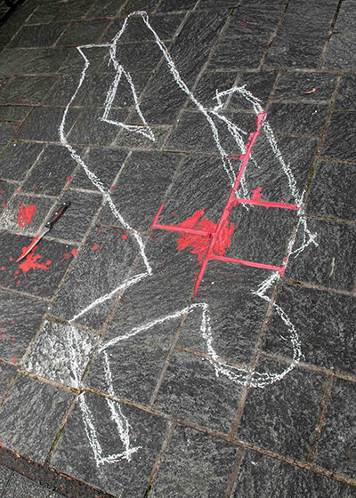 Chalk outline showing where a body had lain on black tiles.