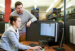 Young female student sitting at desk in Dixson library, using computer while young male looks on