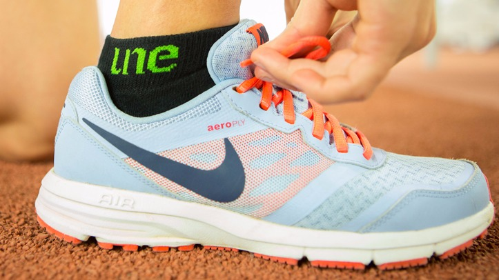 Foot in a Nike Shoe wearing a UNE Sock doing up shoelaces