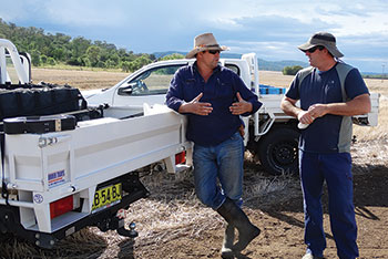 Two men in discussion about their wild pig research, leaning on a ute in a rural area.