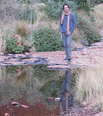 Dr John Ryan standing on a rock near a creek with his reflection on the water.