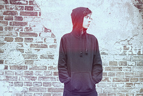 A young person wearing a hooded jacket standing in front of a brick wall