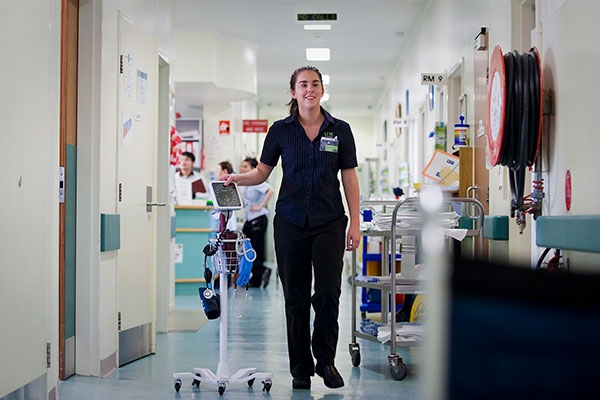 An smiling nurse in a hospital ward with equipment around her.